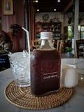 Kallt brygdkaffe i flaska med i is och sirap royaltyfri fotografi