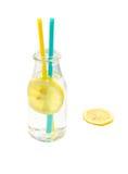 Kallt citronvatten i ett exponeringsglas med två sugrör som isoleras Royaltyfri Foto