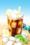Kallt cola- eller iste med citronen på strandbakgrund Arkivfoton