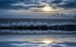 Kallt dimmigt landskap med dramatisk himmel, reflexion i vattnet arkivbilder