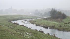 Kallt dimmigt vinterlandskap över på engelska bygd för ström royaltyfria bilder