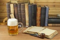 Kallt exponeringsglas av öl på tabellen Koppla av med en Bibeln med ett exponeringsglas av kallt öl Begreppet kopplar av med ett  royaltyfria foton