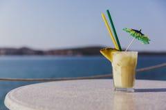 Kallt exponeringsglas av den Pina Colada ställningen på tabellen nära havet royaltyfria bilder