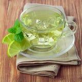 Kallt grönt te med iskuber, skivad limefrukt royaltyfri foto