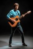 Kallt grabbanseende med gitarren på mörk bakgrund fotografering för bildbyråer