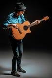 Kallt grabbanseende med gitarren på mörk bakgrund royaltyfri foto