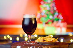 Kallt mörkt öl på julbakgrund Arkivfoto