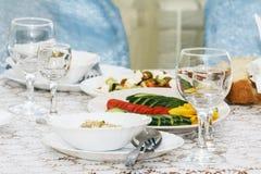 Kallt mellanmål från organiska grönsaker på banketttabellen Tomma vinexponeringsglas för drink, gaffel och sked och ny sallad Sla Arkivfoto