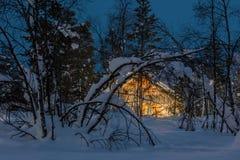 Kallt nattlandskap för vinter, litet trähus med varmt ljus Arkivbilder
