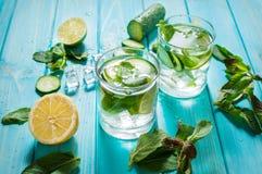 Kallt och förnyande ingett detoxvatten med limefrukt, mintkaramellen och gurkan i ett exponeringsglas på wood bakgrund royaltyfri fotografi
