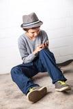 Kallt pojkesammanträde på hans skateboard som rymmer en smartphone Arkivbilder