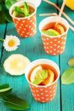 Kallt te med citronskivor och mintkaramell på blå träbakgrund royaltyfri foto