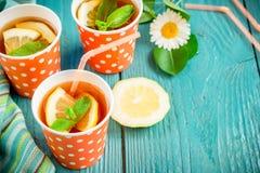 Kallt te med citronskivor och mintkaramell på blå träbakgrund royaltyfri fotografi