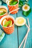 Kallt te med citronskivor och mintkaramell på blå träbakgrund arkivfoto