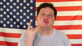 Kallt tecken för manvisning med fingrar och le på bakgrunden av en USA flagga stock video