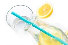 Kallt vatten i ett exponeringsglas av flaskan med citronen som isoleras på vit Fotografering för Bildbyråer