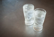 Kallt vatten i ett exponeringsglas med iskuber fotografering för bildbyråer