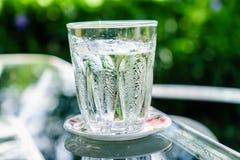 Kallt vatten i exponeringsglas med suddighetsbakgrund Arkivbild