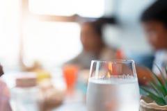 Kallt vatten i exponeringsglas på matställetabellen arkivfoton