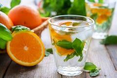 Kallt vatten med apelsinen och basilika royaltyfri bild