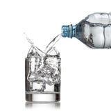 Kallt vattenflaskan häller vatten till exponeringsglas på vit arkivbilder