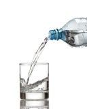 Kallt vattenflaskan häller vatten till exponeringsglas på vit Royaltyfri Foto
