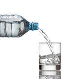Kallt vattenflaskan häller vatten till exponeringsglas på vit Royaltyfria Foton