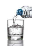 Kallt vattenflaskan häller vattenexponeringsglas på vit bakgrund Royaltyfria Bilder