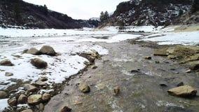 Kallt vattenflod i naturblomma till och med en stenig kanjon med snö på dess banker lager videofilmer