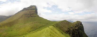 Kallur Lighthouse on Kalsoy Island with green lush cliff landscapes and hikers for perspective in the Faroe Islands, Denmark.