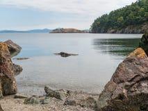 Kalm baaiwater en rotsachtige kust Royalty-vrije Stock Afbeeldingen