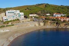 Kalm Mediterraan strand met flatgebouw Stock Fotografie