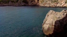 Kalm oceaanwater en een rotsachtige kust stock footage