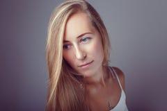 Kalm peinzend Kaukasisch de vrouwenmodel van het blonde jong mooi meisje met lang haar en blauwe ogen in witte kleding Royalty-vrije Stock Foto