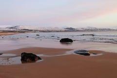 Kalm strand bij dageraad, met sneeuw behandelde heuvels Royalty-vrije Stock Foto