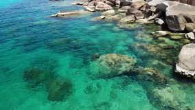 Kalm zeewater dichtbij stenen Vreedzaam blauw zeewater en grijze keien in perfecte plaats voor het snorkelen op Koh Tao Island stock footage
