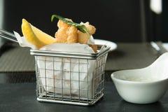 Kalmar und Chips auf einem Korb stockfoto