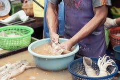 Kalmare einer Mannreinigung in einem Markt Lizenzfreies Stockbild