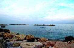 Kalme Adriatische die overzees door massieve rotsen onder de lichtblauwe hemel wordt omringd stock afbeeldingen