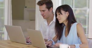 Kalme jonge paarzitting bij lijst die laptop met behulp van stock footage