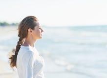 Kalme jonge vrouw die afstand onderzoeken bij kust Royalty-vrije Stock Foto's