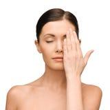 Kalme jonge vrouw die gezicht behandelen met hand Royalty-vrije Stock Afbeelding