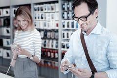 Kalme klanten die apparaten in een winkel testen stock foto
