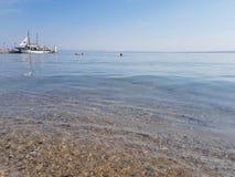Kalme oceaan in de ochtend met boot op de haven en mensen het zwemmen stock afbeeldingen