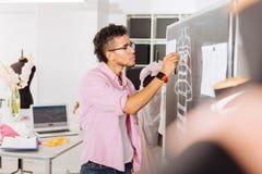 Kalme ontwerper die op het bord trekken terwijl het werken in atelier stock foto