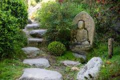 Kalme oosterse tuin met een standbeeld van Boedha Stock Foto's