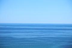 Kalme overzees en blauwe duidelijke hemel Stock Afbeeldingen
