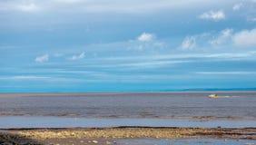Kalme overzees met kleine boot en blauwe hemel stock afbeeldingen