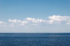 Kalme overzees op een achtergrond van blauwe hemel met cloudsCalmoverzees tegen blauwe hemel met wolken Harmonie van overzeese el royalty-vrije stock foto