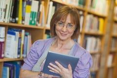 Kalme rijpe bibliothecaris die met haar tablet in bibliotheek werken stock fotografie